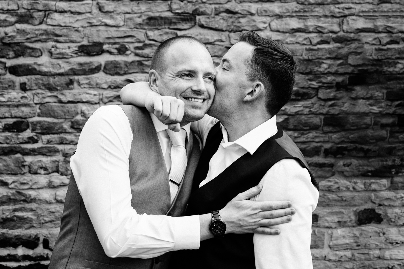Image of groom and best man hugging at wedding