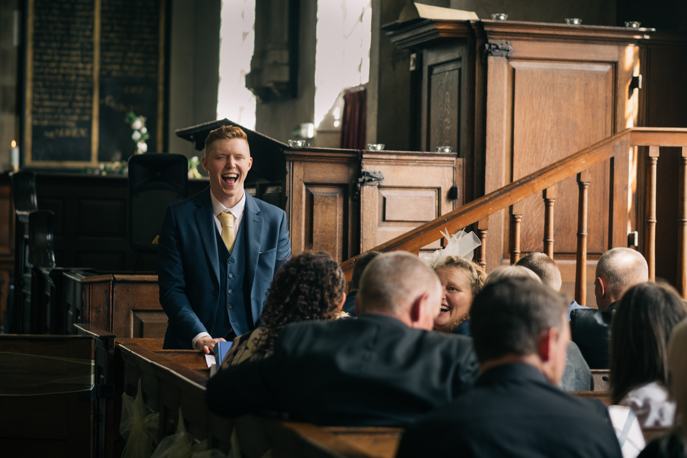 Image of groom laughing with guests at wedding in yorkshire