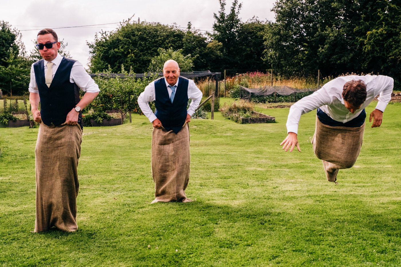 Image of wedding guests during a sack race