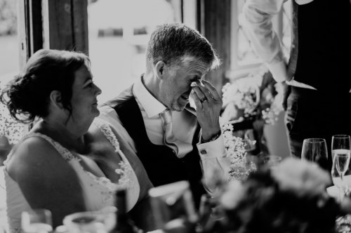 Groom wipes a tear from his face during wedding speeches
